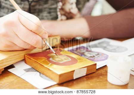 Iconography. woman painter hand with brush paints a new Mother of God icon at workshop poster