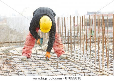 construction worker making reinforcement with metal rebar rods at building site poster