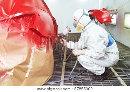 auto repair worker painting a red car in a paint chamber during repair work