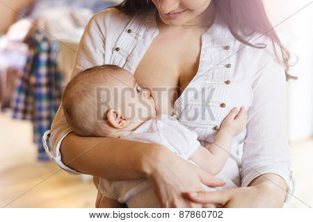 Mother breastfeeding her little baby girl in her arms. poster