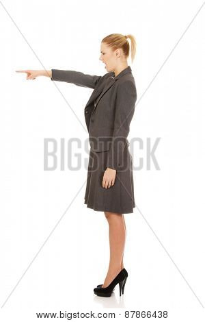 Angry young businesswoman pointing aside.