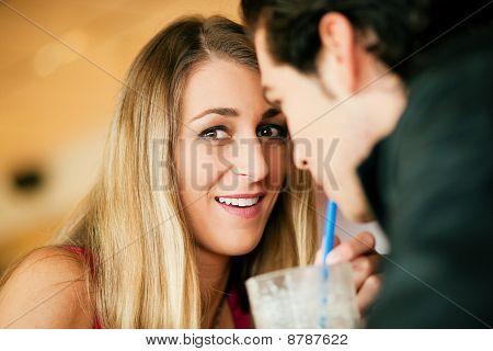 Couple in restaurant drinking milkshake