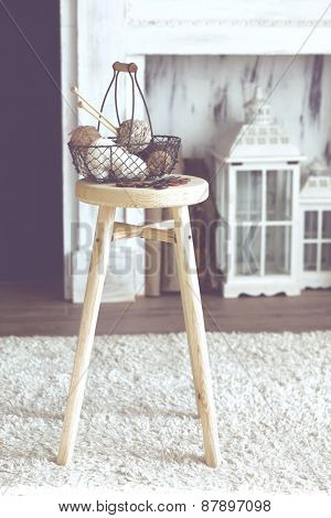 Vintage knitting needles, scissors and yarn inside old wire basket on wooden stool near fireplace, still life photo with soft focus