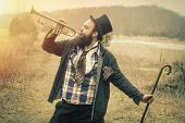 Stylish bearded gypsy plays trumpet on a wilderness path poster