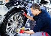 Man worker washing car's alloy wheels on a car wash  poster