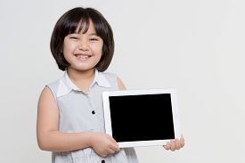 Little asian girl smiling and holding tablet computer on isolated background