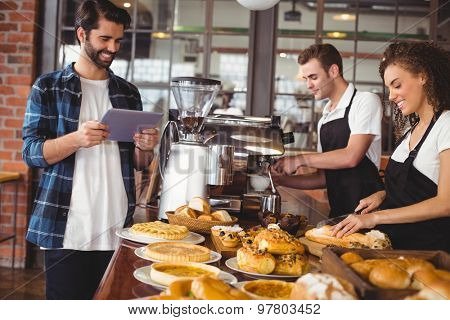 Smiling colleagues serving customer with tablet at coffee shop