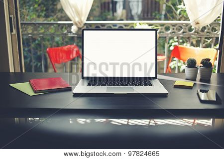Freelancer needs workstation workplace with laptop, smartphone, note book and pot of flowers