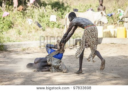 BOR, SOUTH SUDAN-DECEMBER 4, 2010: Unidentified Dinka tribesman throws another man to the ground in a wrestling match north of Bor, South Sudan