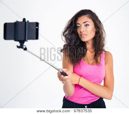 Portrait of a pretty young woman making selfie photo on smartphone with stick isolated on a white background