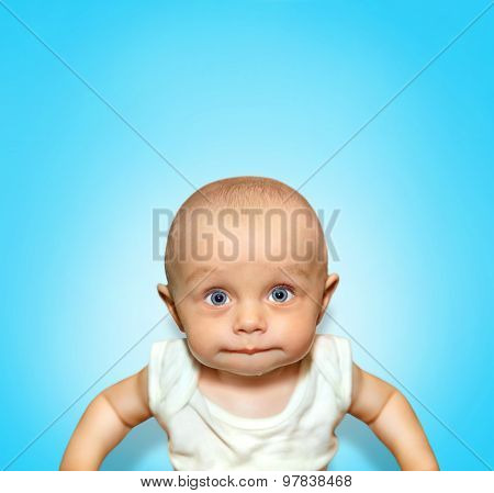Funny portrait of an adorable baby boy sucking lips with blue eyes on background