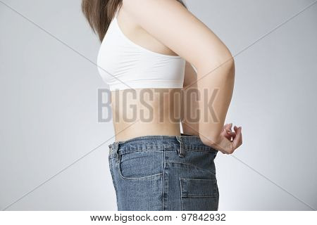 The concept of weight loss. Beautiful slender female body. Young woman in jeans large size. poster