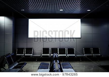 Commercial board with clean space in waiting of airport hall with empty chairs