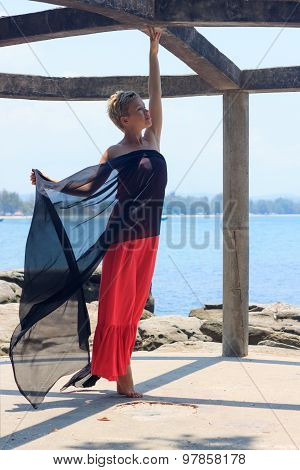 Young Woman In Red Dress Standing On Tiptoe Inside Round Alcove On Sunny Day With Seaview At Backgro