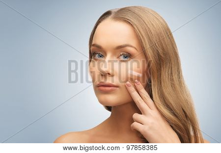 people, beauty, cosmetics and makeup concept - beautiful woman applying pale and dark foundation tone to face over gray background