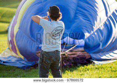Hot-air balloon crew pulling ropes and deflating balloon