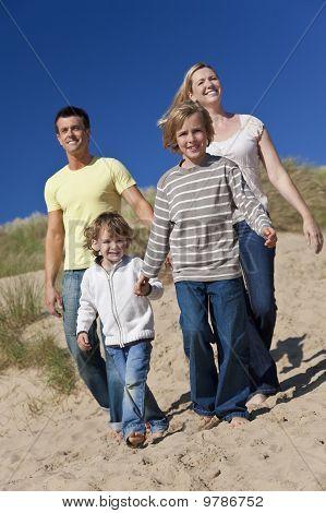 Mutter, Vater und zwei jungen, die zu Fuß, Spaß am Strand