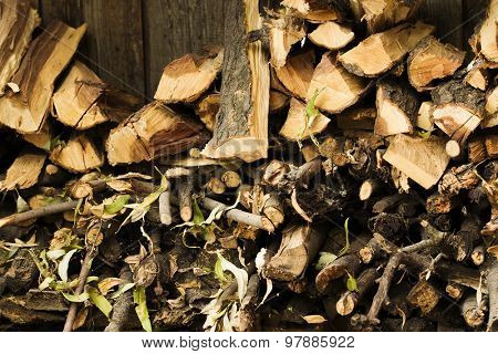 Background of dry chopped firewood and branches log in a pile