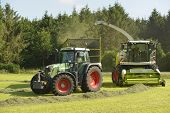 Agriculture forage harvester and transport grass with green tractor and grass trailer poster