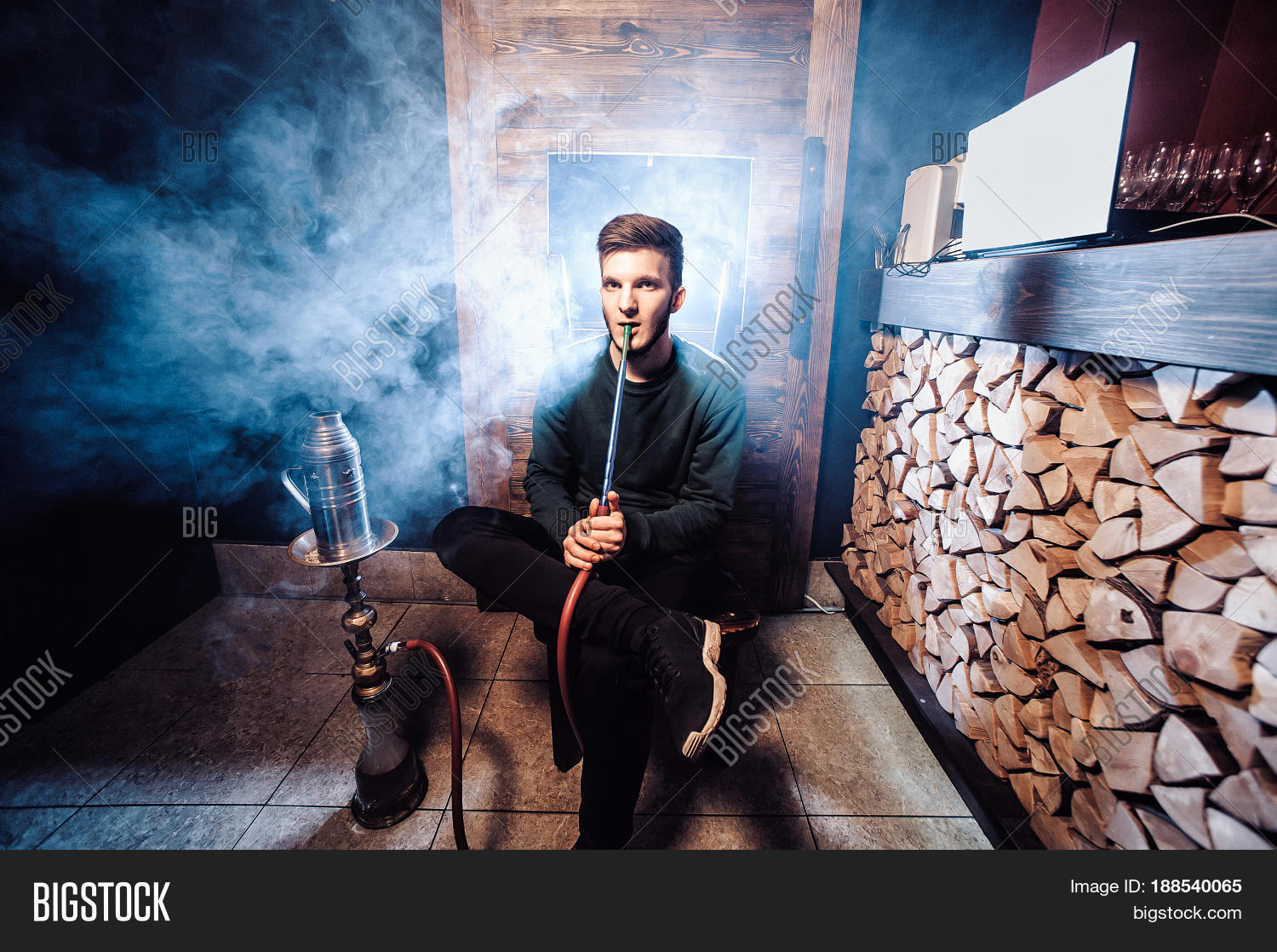 Young handsome guy smoking hookah alone closeup