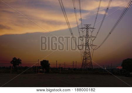 Light towers and high-voltage lines with sky on sunset.