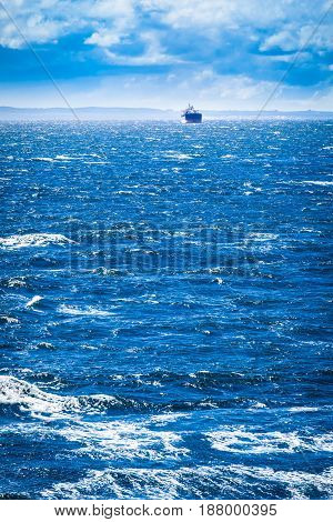 Distant cargo vessel at sea horizon with dramatic sky and waves (copy space)