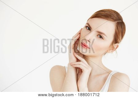 Portrait of young beautiful girl looking at camera touching face over white background. Facial treatment. Beauty cosmetology and skincare. Copy space.