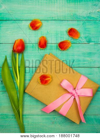 Kraft envelope tied with a pink ribbon on wooden background with tulips copy space for text