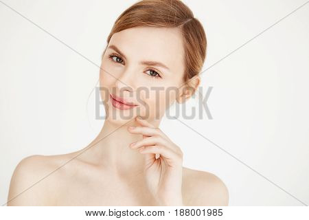 Portrait of naked beautiful girl with natural make up smiling looking at camera over white background. Health and beauty lifestyle. Copy space.