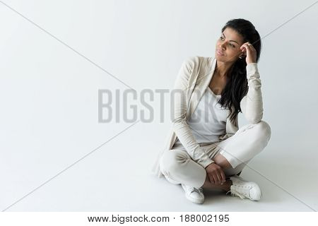 Attractive Pensive African American Woman Sitting Isolated On White With Copy Space