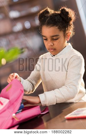 african american schoolgirl packing backpack and preparing for school elementary school student concept