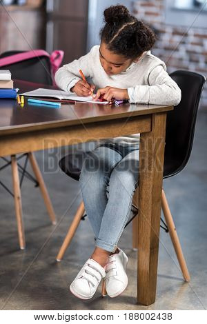 Full Length View Of Cute African American Girl Girl Sitting At Table And Doing Homework
