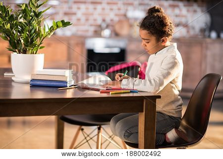 Side View Of Cute African American Girl Sitting At Table And Doing Homework