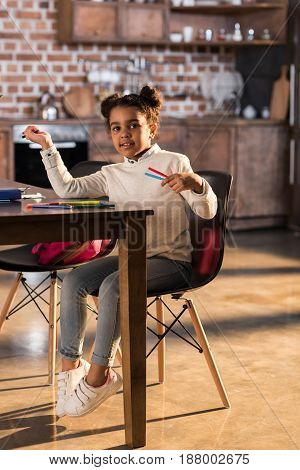 Smiling Little Girl Sitting At Table And Drawing With Felt Tip Pens, Doing Homework Concept
