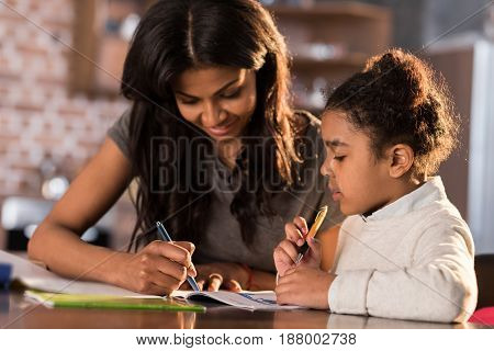 Mother And Cute Little Daughter Sitting At Table And Doing Homework Together At Home, Homework Help