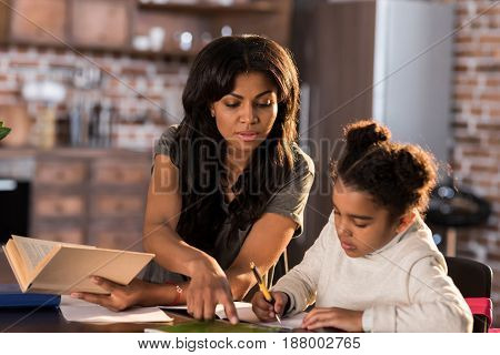 Mother And Daughter Learning Together At Table And Doing Homework, Homework Help Concept