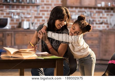Smiling Little Girl Hugging Happy Mother At Home