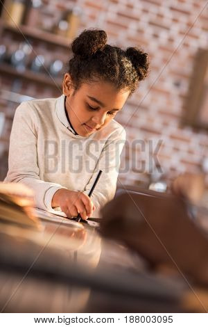 Portrait Of Focused Little Girl Doing Homework At Home