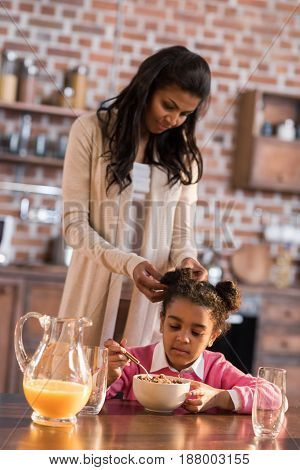 Mother Doing Hairstyle To Little Girl During Breakfast At Home