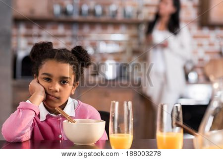 Portrait Of Upset Little Girl Having Breakfast At Home