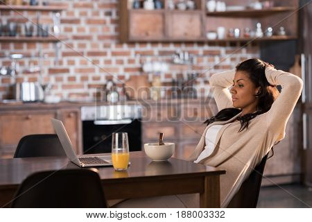 Young African American Woman Having Breakfast And Using Laptop At Kitchen