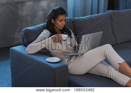Young African American Woman Drinking Coffee While Using Laptop At Home