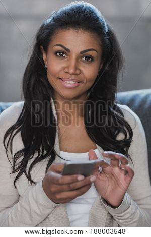 Young African American Woman Sitting On Sofa And Typing On Smartphone At Home
