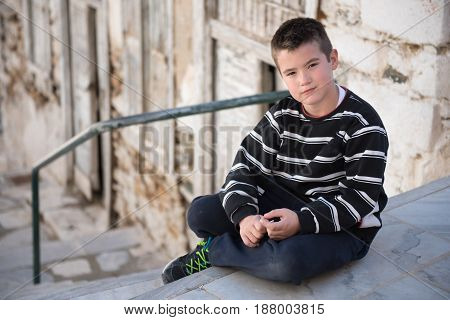 Portrait Of A Boy In Black And White Clothes Posingsitting In The Street Of A Traditional Small Stre