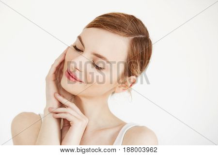 Portrait of young beautiful girl smiling with closed eyes touching face over white background. Facial treatment. Beauty cosmetology and skincare. Copy space.