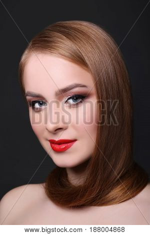 Beauty model on black background, fashion shooting. Woman with makeup, perfect skin and hair posing to camera at studio