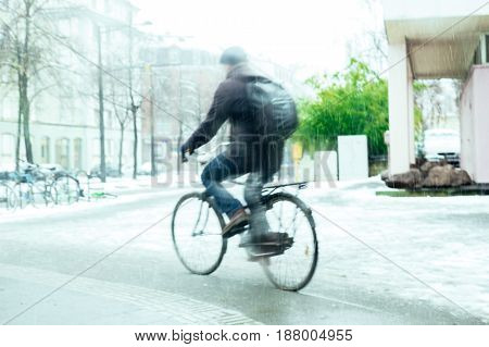 Sihlouette of adult cyclist blurred motion on snow on a snowy winter day