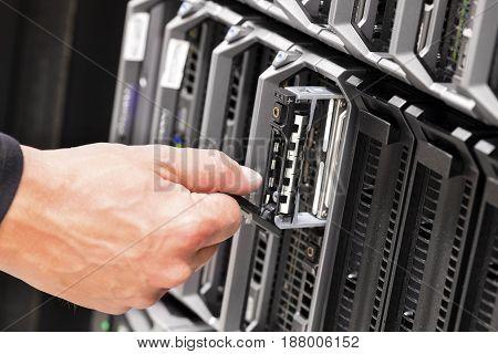 Closeup of IT technicians hand repairing server at data center