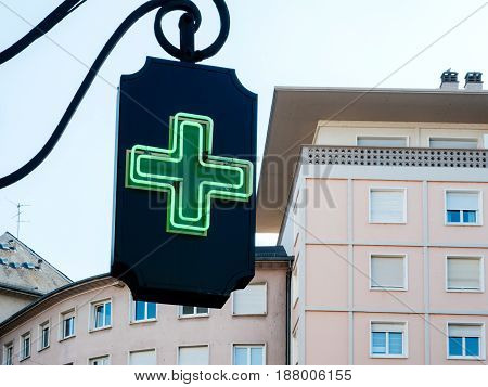 Neon sign drugstore pharmacy Pharmacie with apartment building in the background in French city