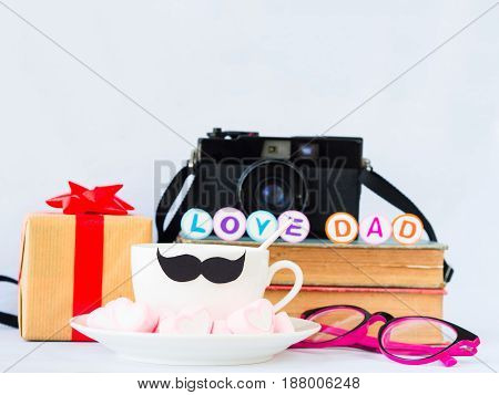 Father's day concept. LOVE DAD alphabet on stack of books gifts glasses retro camera tea cup with black Mustache and sweet marshmallow in the shape of heart on white background
